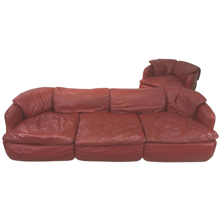 We have one brick red/cordovan leather sofa and matching armchair designed by the Italian architect, Alberto Rosselli in 1972 for Saporiti Italia. Two pieces total. Price shown is for the sofa and the chair together.