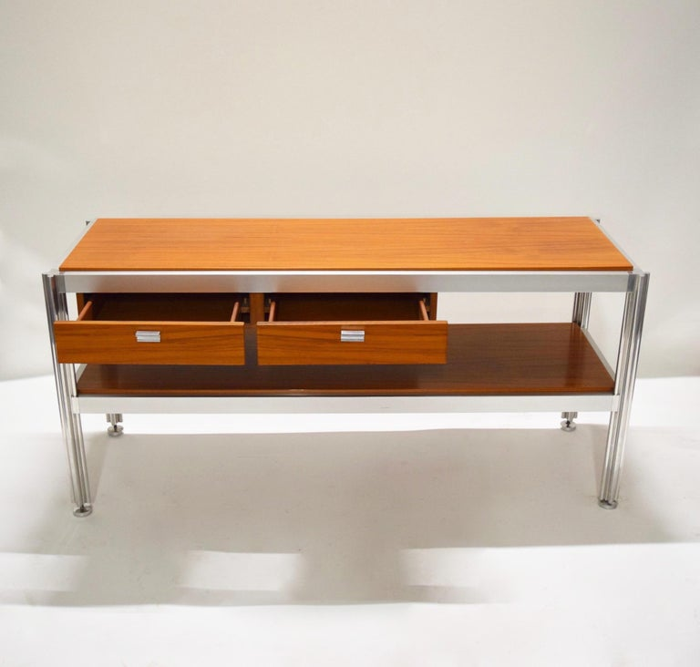 Two-tier console table designed by Jens Risom, comprises a polished aluminum frame and pulls, channeled legs in the shape of a clover, four round feet that can individually adjusting height, two pull-out drawers on the upper left section, and inset