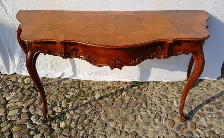 In carved walnut wood, entirely veneered in rootwood. Shaped top, drawer on the front and finely carved band.
