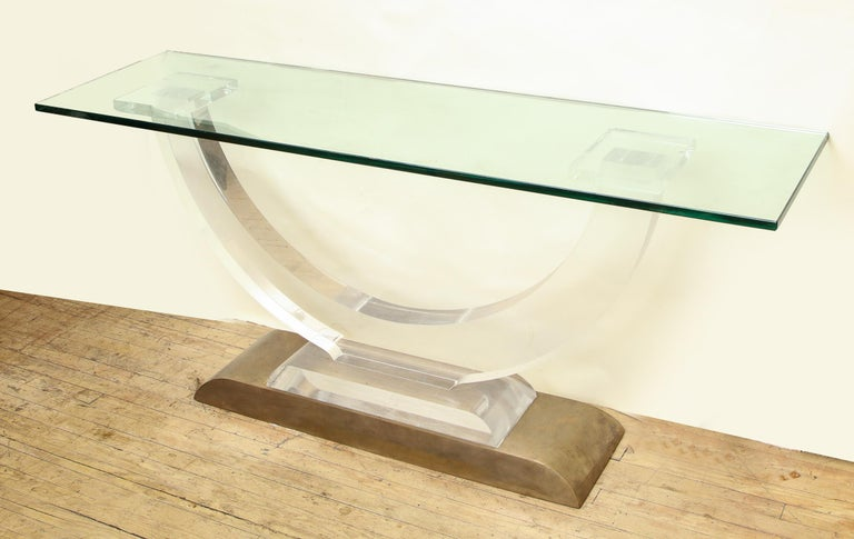 An Architectural console table Lucite and glass with a heavy brass base, 1970s.