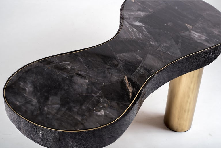 The constellation coffee table is whimsical and elegant with its galactic inspired shaped. This piece can also double as a bench. The top is inlaid in a beautiful Black Quartz semi-precious stone that has incredible tonalities in it and details. The