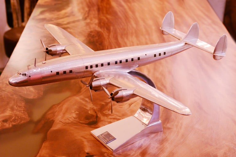 Aircraft model constellation Lockheed L1049, reduced model, lightweight wooden frame, handcrafted in aluminum foil, with engraved  metal rivets. Measures: Base height: 26cm.