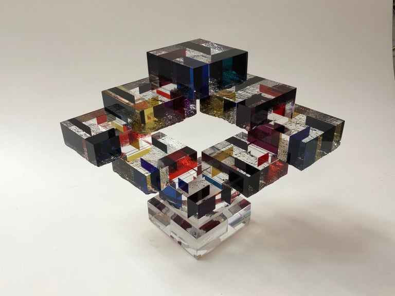 This is a very interesting and well crafted table sculpture. The Lucite cubes have multiple colors and texture on one side, they are arranged in an outward and upward design. Signed and dated. Name of sculpture is