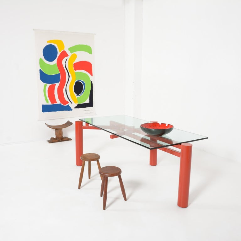 This constructivist dining table was designed by Christophe Gevers and edited by be.classics in 2001. The heavy red-orange metal base consists of 3 legs that can be placed in different positions so that the rectangular glass top can be changed into