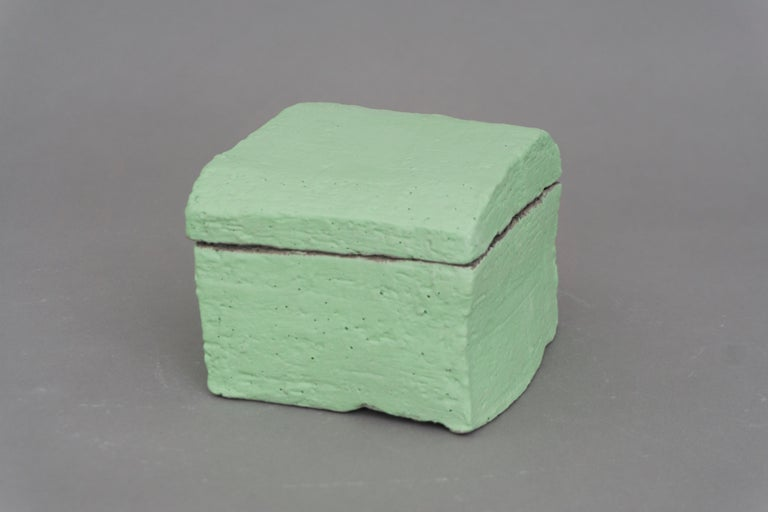 Unique square container by Christine Roland with a lid. Made of grey stoneware with a fresh pale green engobe by designer Christine Roland. Matt finish and a heavy feel. Store your precious items!  'Christine Roland is a Berlin-based, Danish