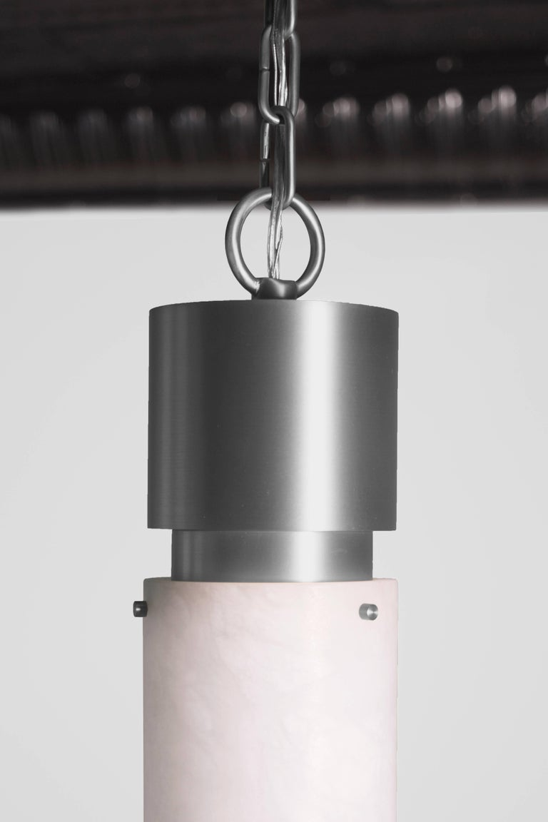 This contemporary light made of brushed nickel and alabaster is part of the Orphan Work brand and can be used as a ceiling pendant or flush mount. 