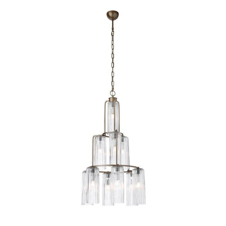 Ten downward-facing, grooved lampshades in transparent glass are distributed in the three metal tiers of this exquisitely modern chandelier. Its Silhouette creates a pyramidal shape and hosts 10 tubular LED sources (each E14 4W) that provide a