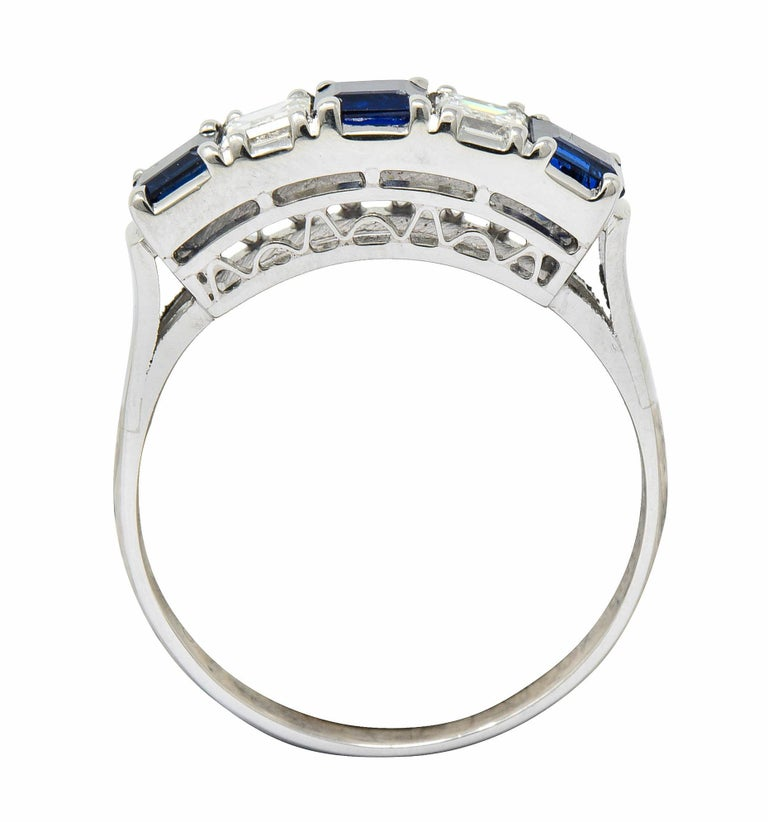 Band ring is set to front by rectangular cut sapphire and rectangular step cut diamonds  Sapphires are a well-matched medium-dark royal blue and weigh in total approximately 0.91 carat  Alternating with diamonds weighing in total approximately 0.40