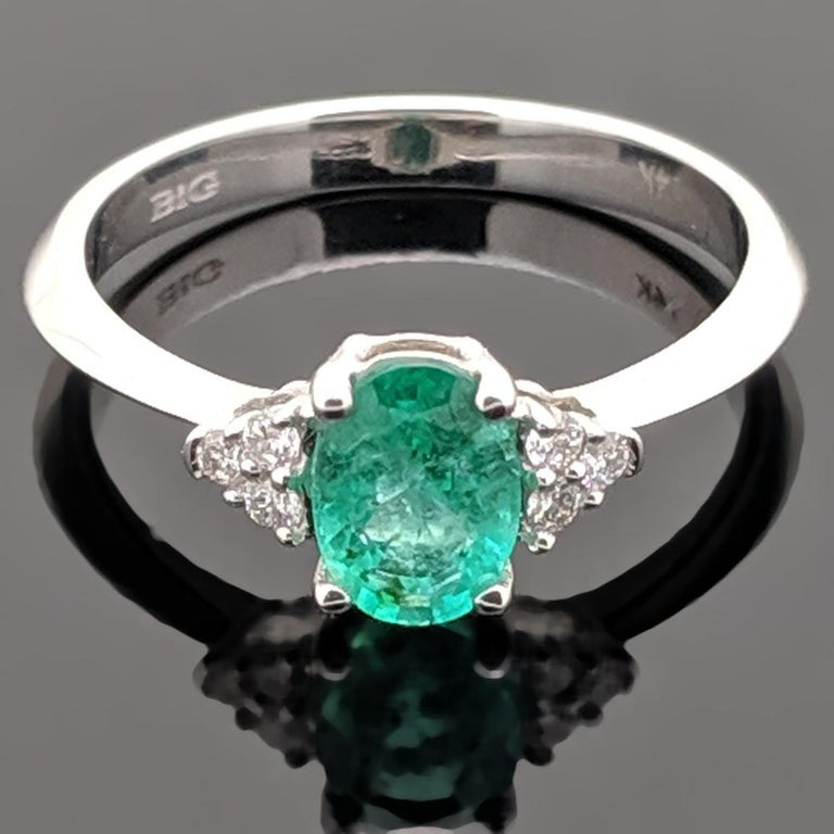 This is a 14kt white gold ring with an oval-shaped emerald at an estimated weight of 0.72ct and six side diamonds estimated at 0.08cttw with sleek knife's edge shoulders. Estimated weight of gold is 2 gr.   We will size it for you.