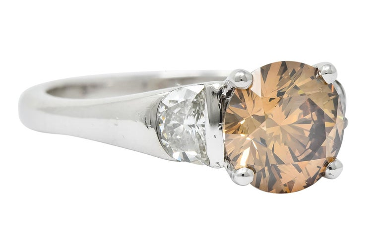 Centering a fancy colored round brilliant cut diamond weighing 2.11 carat; VVS2 in clarity and natural in color as an evenly dark orangey-brown  Basket set and flanked by two flush set half moon cut diamonds weighing in total 0.64 carat, J/K in