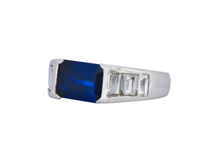 Sleek band style ring centering an emerald cut sapphire, half bezel set East to West, weighing 2.18 carats; enticing royal blue in color  Flanked on each side by channel set baguette cut diamonds weighing approximately 1.14 carats total, G/H color