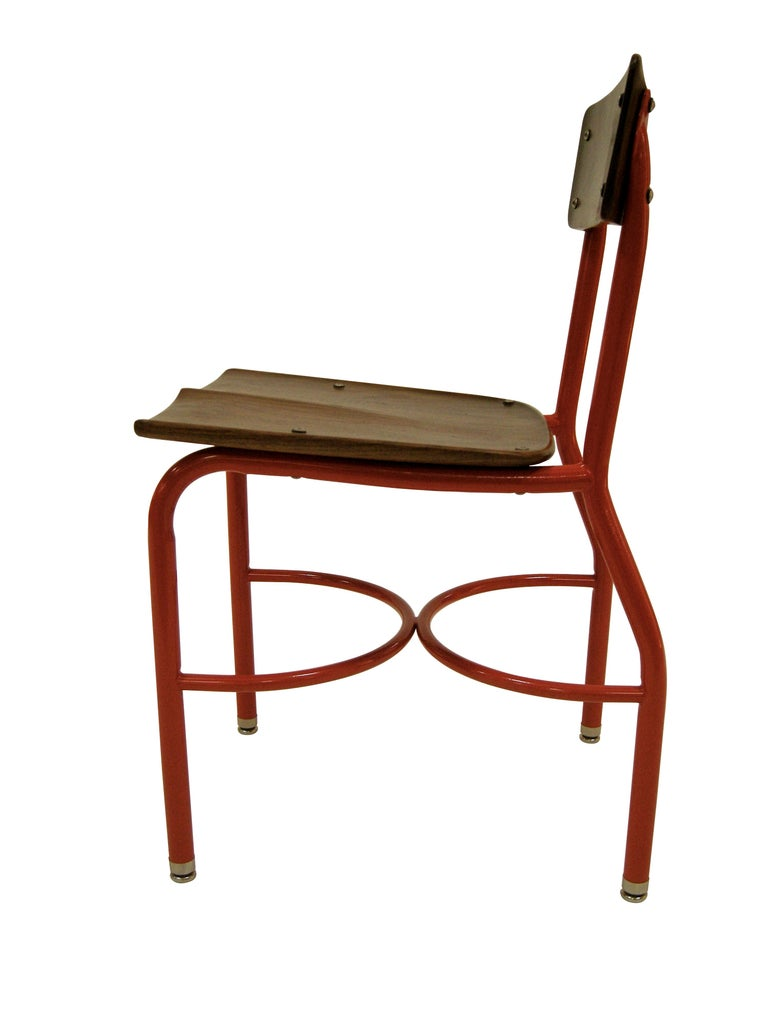 This found vintage school house chair has been customized into a contemporary side chair. The frame was stripped and subsequently powder coated red as a nod to the one room