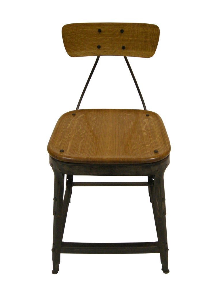 This found factory chair has been refinished and transformed into a contemporary side chair. The frame was stripped, given a blackened patina and a hand rubbed waxed finish. The wooden seat and back are hand hewn from salvaged oak and fastened to