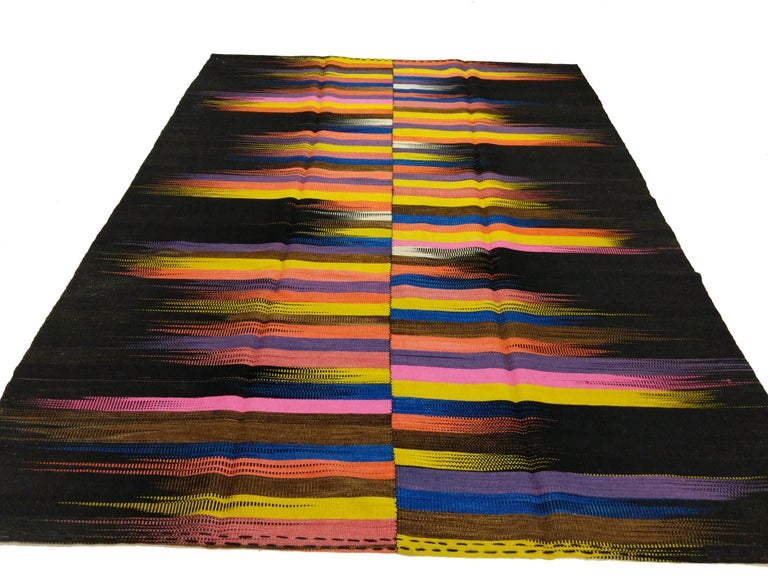 A stunning graphic contemporary Anatolian Kilim of great material quality, distinguished by a black wool background punctuated by a dazzling array of rich colors contained in flame-like brushstrokes, expertly handwoven to contrast. Truly a 21st