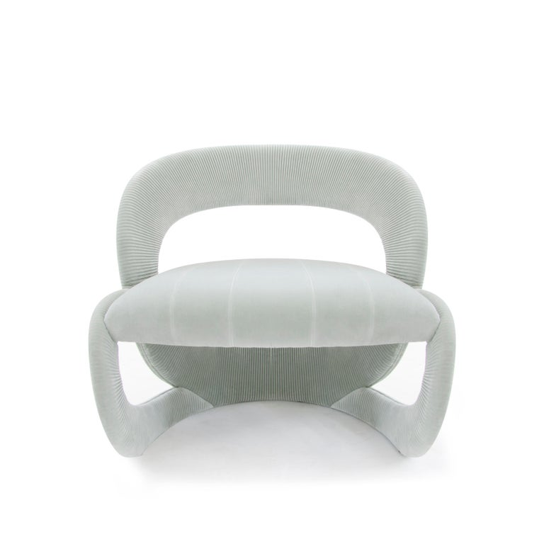 Armchair Penelope, suitable to furnish modern living areas, can be also chosen as a unique and refined item for bedrooms. It is characterized by a sinuous and soft structure composed of multilayer wood upholstered with Artic light-blue velvet able