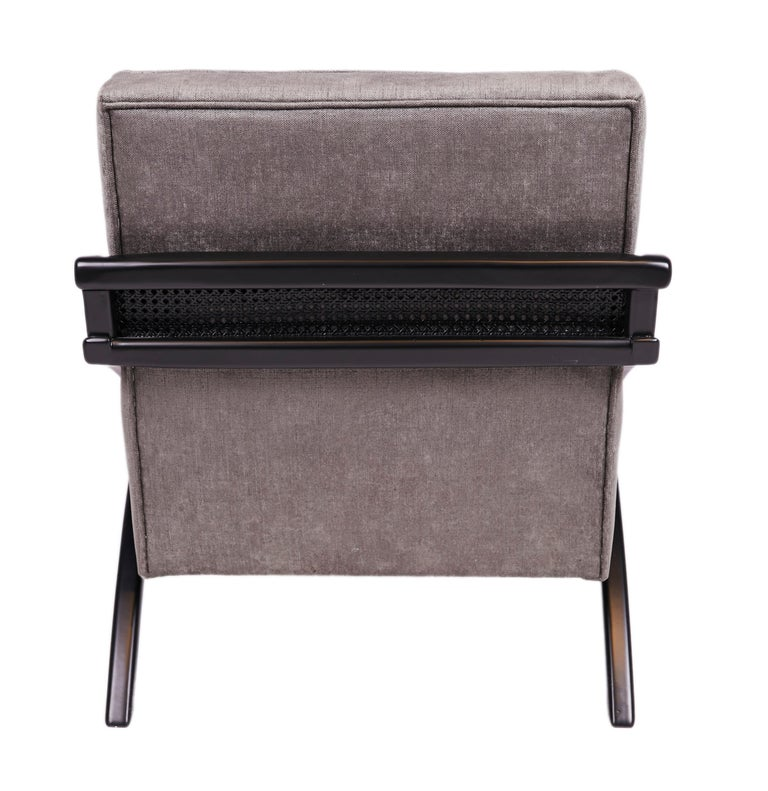 Marrying tradition and modernity - the frame lounge chair features a solid wood frame with rattan arms tastefully wrapped behind. Gleaning influence from the Art Deco movement - the fixed seat and back cushions are upholstered in gray velvet a