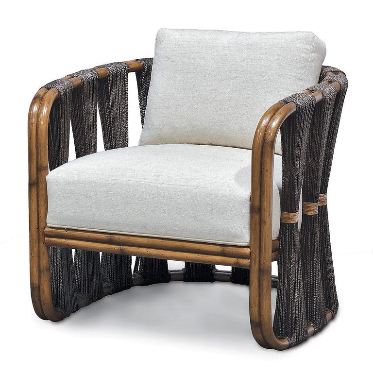 An expertly crafted armchair made of premium materials and a unique contemporary design makes for a remarkable piece.  Natural finished black rope is wrapped and bundled in a sophisticated, contemporary manner around the a-grade rattan frame of the