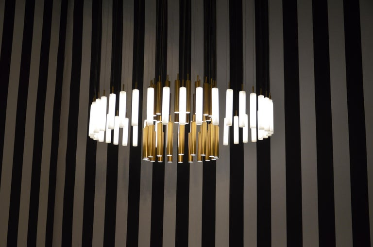 The Art-Déco rainy day bespoke chandelier is designed by Sylvie Maréchal and it is entirely manufactured in France. This chandelier is made of 80 Limoges Porcelain tubes of which 40 are fine golden tubes and 40 are white tubes. The tubes are