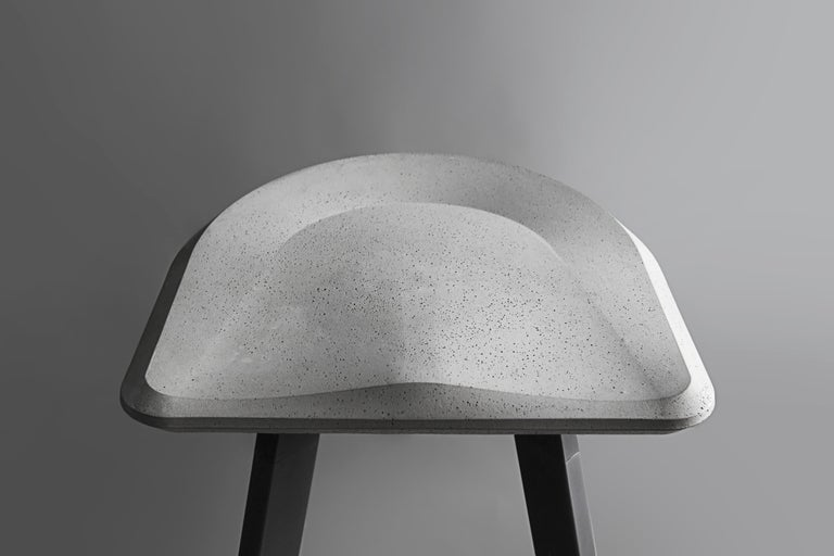 'A' is a bar stool made of concrete and aluminium by Bentu Design  Dimensions: H 76.5cm x 46.5 x 46.5 cm   Bentu Design's furniture derives its uniqueness from the simplicity of its forms and its materials. Designed and manufactured by the