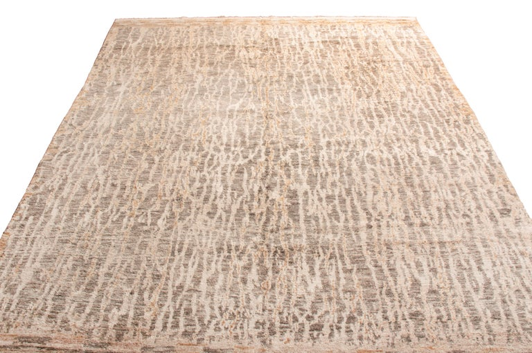 Hand knotted in high quality wool, this contemporary wool rug originates in India with an individualistic bark-like field design. While similar pieces employing hues of beige and stone gray extend throughout the guard border, the vertical guard