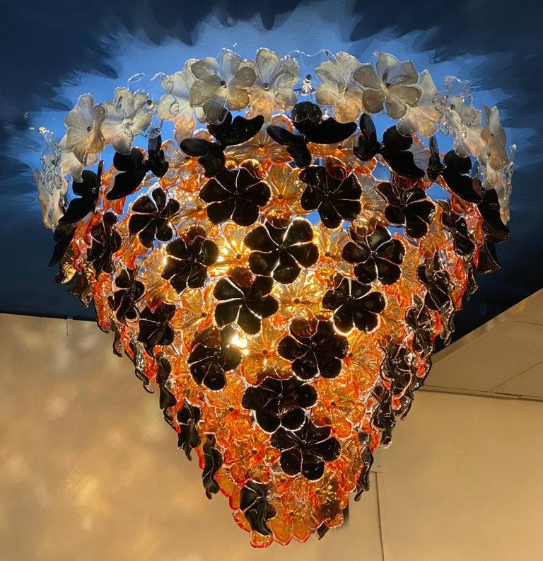 Striking contemporary Murano glass chandelier composed by dozens black orange and white hand blown flowers and by Galleria Veneziani. Available also a pair.