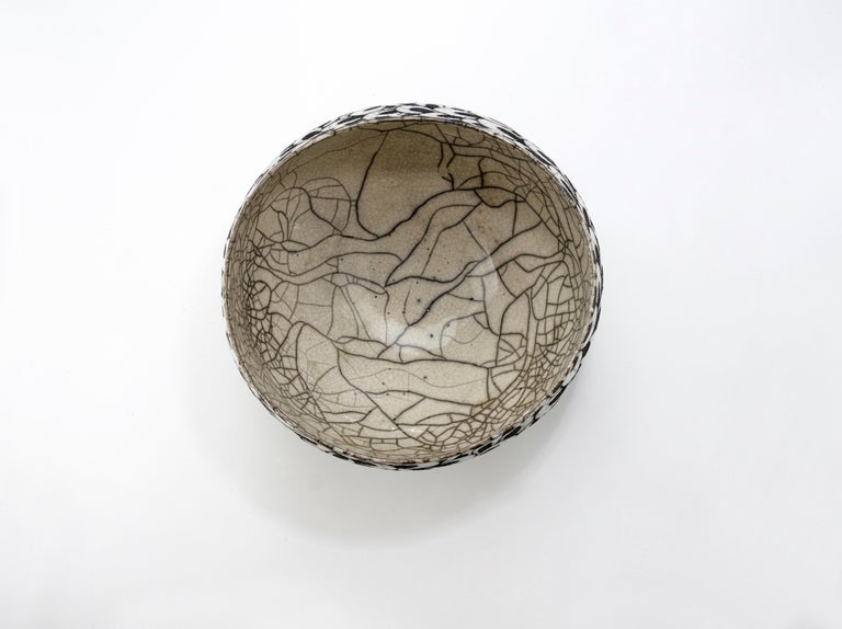 This bowl is a decorative contemporary black and white ceramic raku coupe