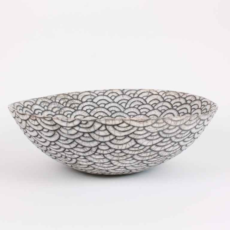 Decorative contemporary black and white ceramic raku coupe by artist Camille Campignion. Inspired by the Japanese seigaiha (or wave motif), the artist has individually engraved, freehand, hundreds of waves on the hand-coiled piece. The distinctive