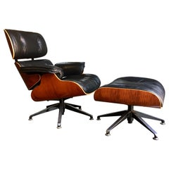 Contemporary black leather and plywood lounger with matching footstool