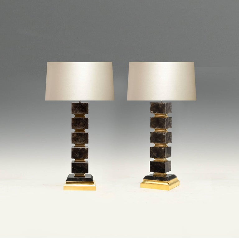 A pair of fine block form dark rock crystal quartz lamp with polish brass insert and base, created by Phoenix Gallery, NYC. Available in nickel plating and antique brass finished.  To the rock crystal: 20 inch/H. (Lampshade not included).