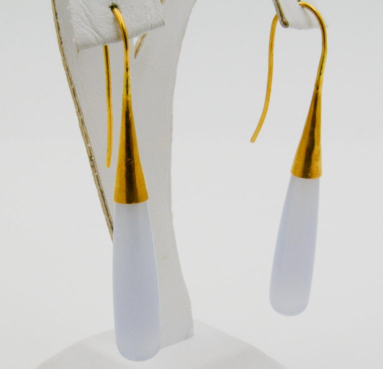 These contemporary 24k yellow gold drop earrings feature 38 x 8mm Chalcedony stones that have a slightly transparent sheen.