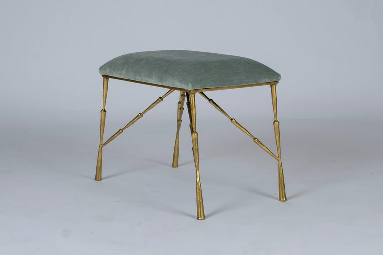 A contemporary brass ottoman upholstered in a striated pale aqua green velvet. Also available C.O.M.