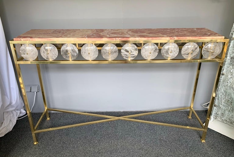 Contemporary brass console table inspired in a neoclassical Louis XVI style with large pieces of rock crystal natural stone and rare red onix top, different from marble. Small Italian workshop, few exclusive and quality production.