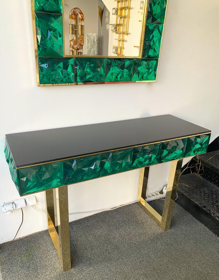 Contemporary wall mirror and console set, full brass and large pieces of green emerald Murano glass with relief diamond point. Small artisanal workshop. The mirror can be hang horizontally also. Console Measurements W 125 x D 43 x H 79 centimeters.