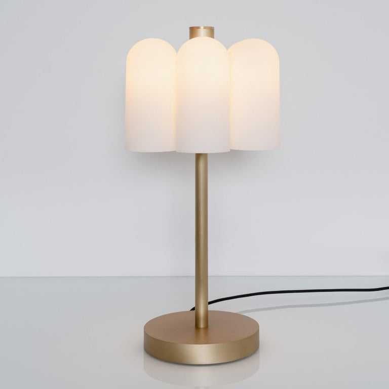 Contemporary brass table lamp by Schwung Dimensions: W 31 x D 31 x H 65 cm Materials: Brass, frosted glass  Finishes available: Black gunmetal, polished nickel, brass   Schwung is a German word, and loosely defined, means energy or momentum of a