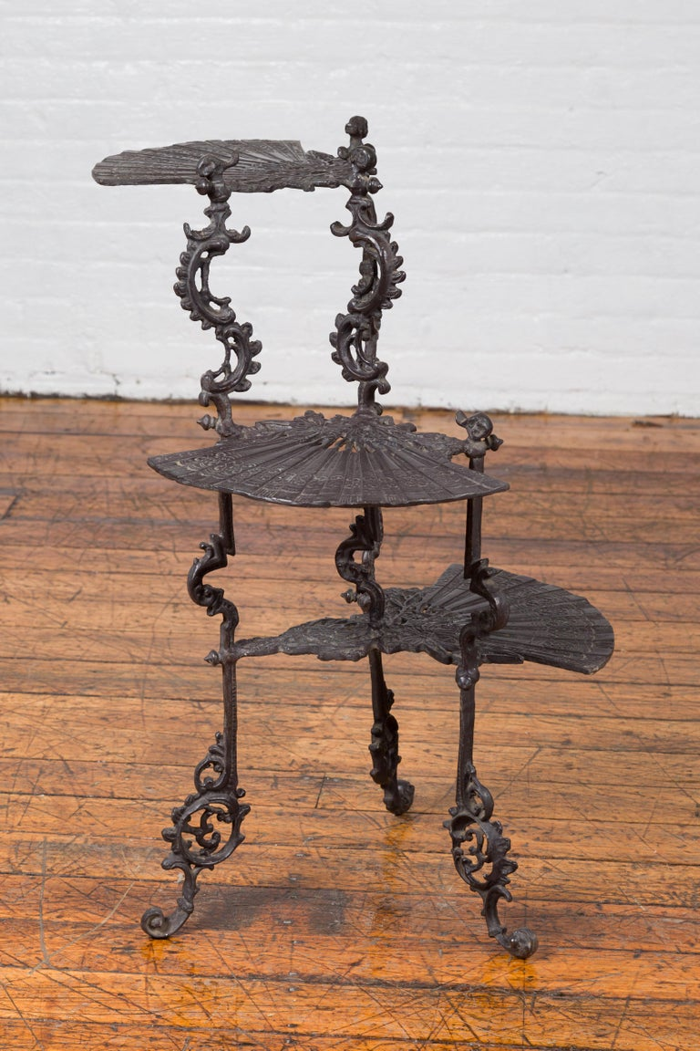 A contemporary bronze display stand with fan shelves and Rococo style scrolling motifs. Created with the traditional technique of the lost-wax (à la cire perdue) that allows a great precision in the details, this display stand captures our attention