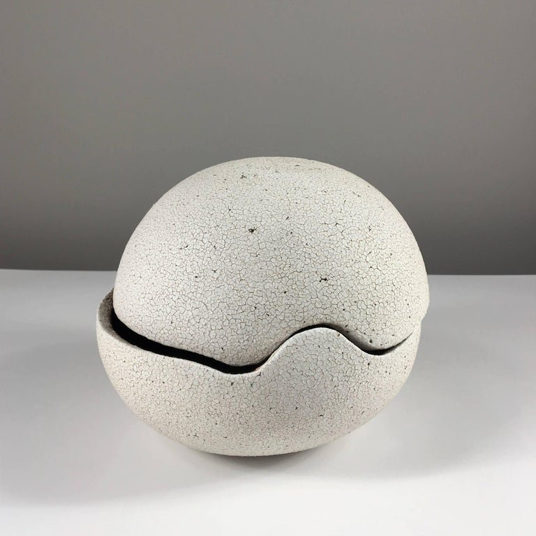 Contemporary ceramic artist Yumiko Kuga's glazed stoneware orb covered vessel no. 196 is part of her Crackle series. All of the pieces in this series are hand-built and 100% handmade so they are one-of-a-kind and thus vary slightly from one another.