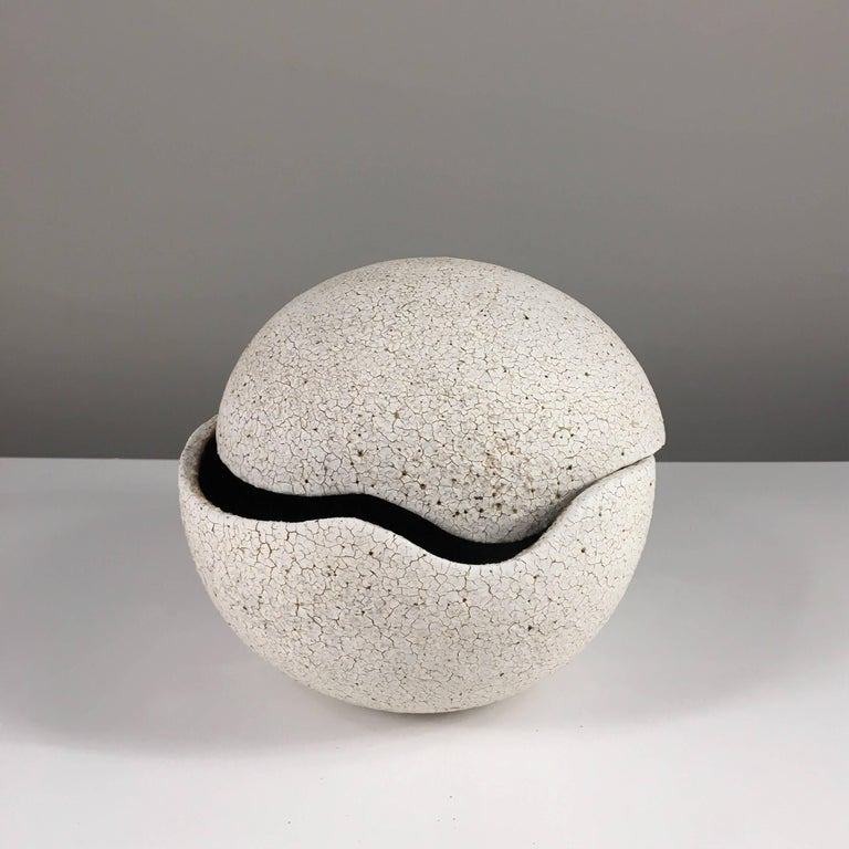 Contemporary ceramic artist Yumiko Kuga's glazed stoneware orb covered vessel no. 199 is part of her Crackle series. All of the pieces in this series are hand-built and 100% handmade so they are one-of-a-kind and thus vary slightly from one another.