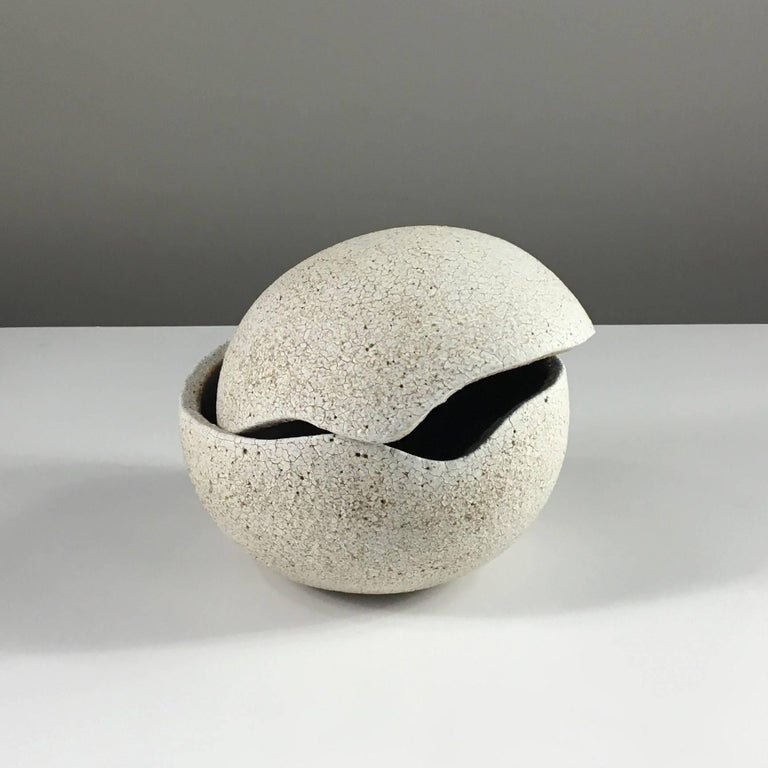 Contemporary ceramic artist Yumiko Kuga's glazed stoneware orb covered vessel no. 200 is part of her Crackle series. All of the pieces in this series are hand-built and 100% handmade so they are one-of-a-kind and thus vary slightly from one another.