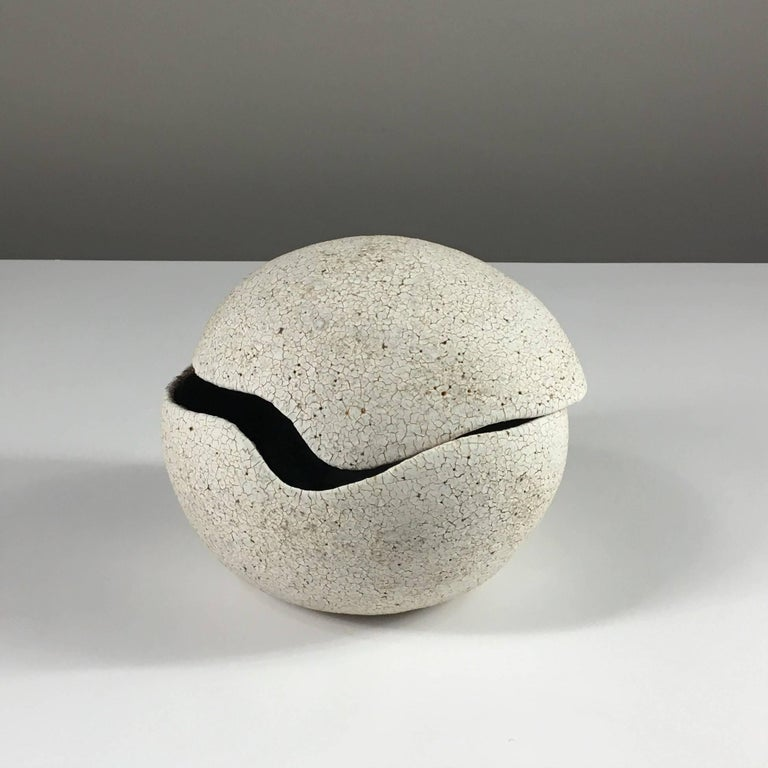 Contemporary ceramic artist Yumiko Kuga's glazed stoneware orb covered vessel no. 204 is part of her Crackle series. All of the pieces in this series are hand-built and 100% handmade so they are one-of-a-kind and thus vary slightly from one another.