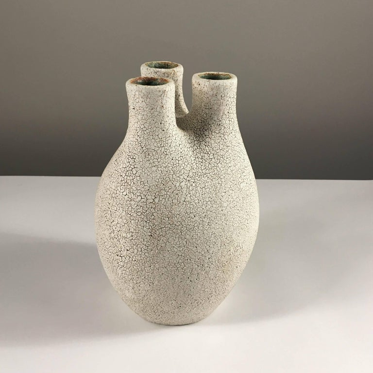 Contemporary ceramic artist Yumiko Kuga's glazed stoneware tri-neck vase no. 184 is part of her Crackle series. All of the pieces in this series are hand-built and 100% handmade so they are one-of-a-kind and thus vary slightly from one another. All