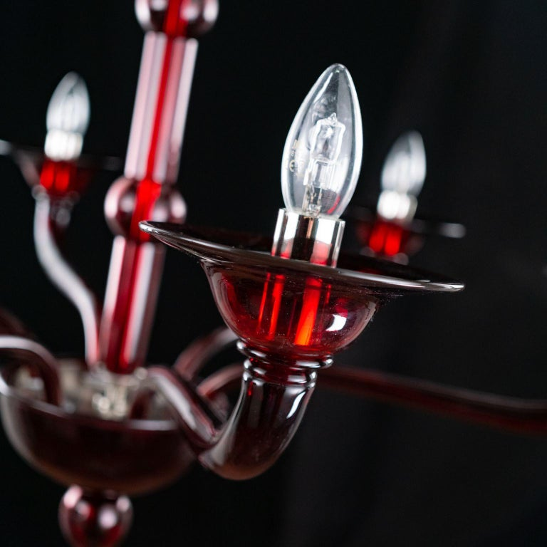 Multiforme Tobia chandelier 6 lights. red Murano glass with castle arms climbing arms. The blown glass chandelier Tobia harks back to the design typical of the first half of the 20th century. This lighting work is characterized by a tube-shaped
