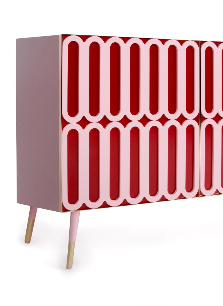 A colorful buffet in pink matte body and a pink matte pattern over a glossy royal red surface, elevated by a brass presence. Handmade by highly skilled European artisans.  Available in stock in Royal red and pink lacquer or can be made to order with