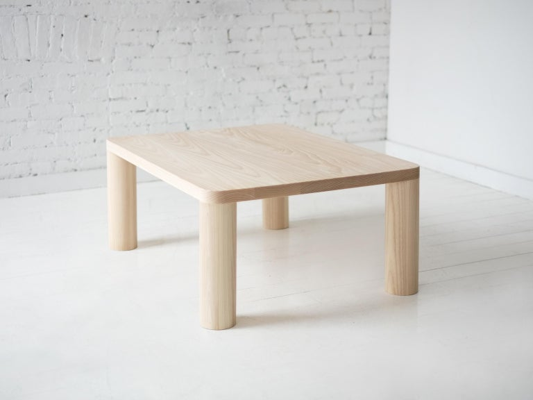 This contemporary, minimal wooden coffee table features four large round legs that seamlessly meet and define the radii of the top, a quiet but powerful detail.   Made to order in custom sizes, shapes, materials and finishes. Hard maple and walnut