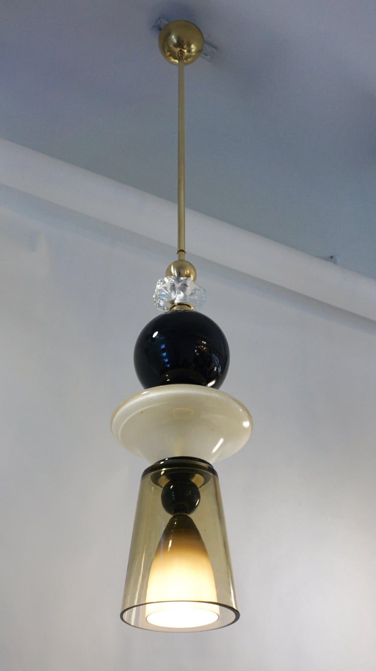 Fun and elegant Italian pendant chandelier, entirely handcrafted, of organic modern design consisting of a succession of elements: black opaline glass and brass spheres, a hand-cut jewel like rock glass decoration, a saucer shaped ivory white mouth