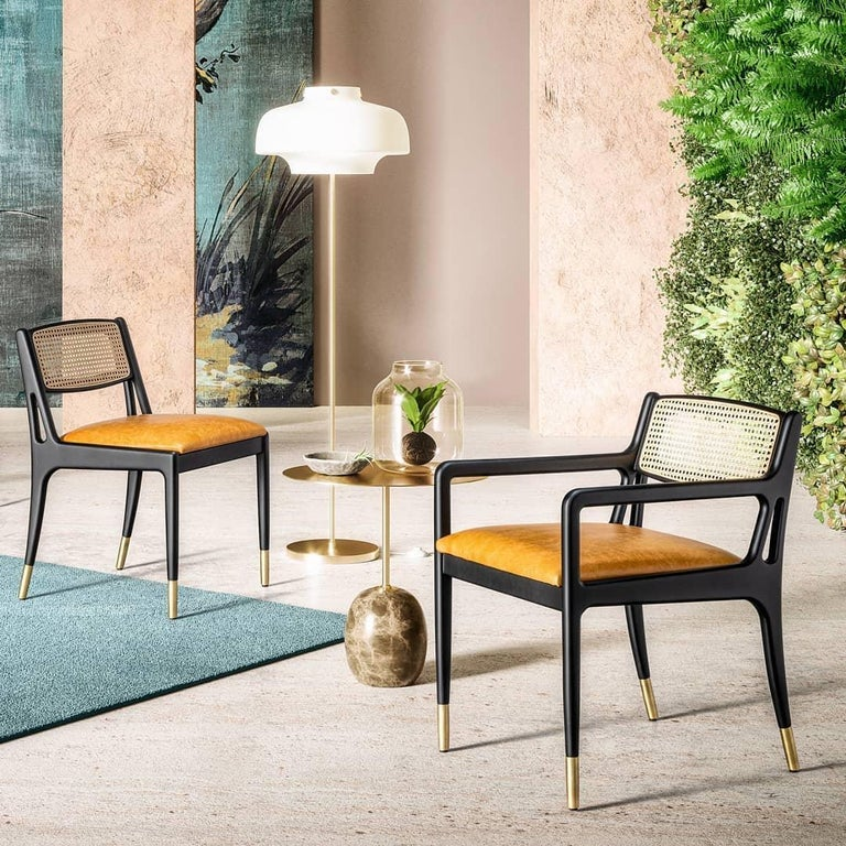 A Mid-Century Modern style dining chairs in ebony finished frame. Ebony finished wood frame. Backrest in natural woven cane. Seat in chocolate brown leather.   Dimensions: W 47 cm x D 61 cm x H 77 cm Materials: Wood, leather, rattan Seat H 46