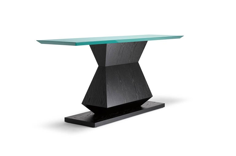 With its angular, symmetrical base and bevelled top this design is available as a console, occasional or dining table, with the option of specifying a lacquer colour to the top. Shown here in ebonised oak with a turquoise *lacquered top.  Each