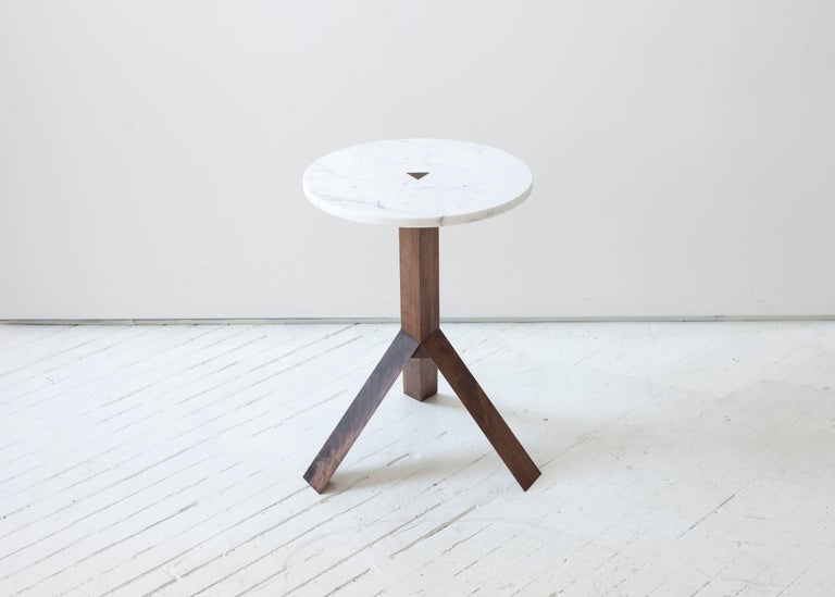 Three angular wood legs split off from a triangular centre post to elevate the small geometric stone tops of this side table. A triangular wood tenon pierces the centre of the table top, communicating the construction and creating a subtle, flush