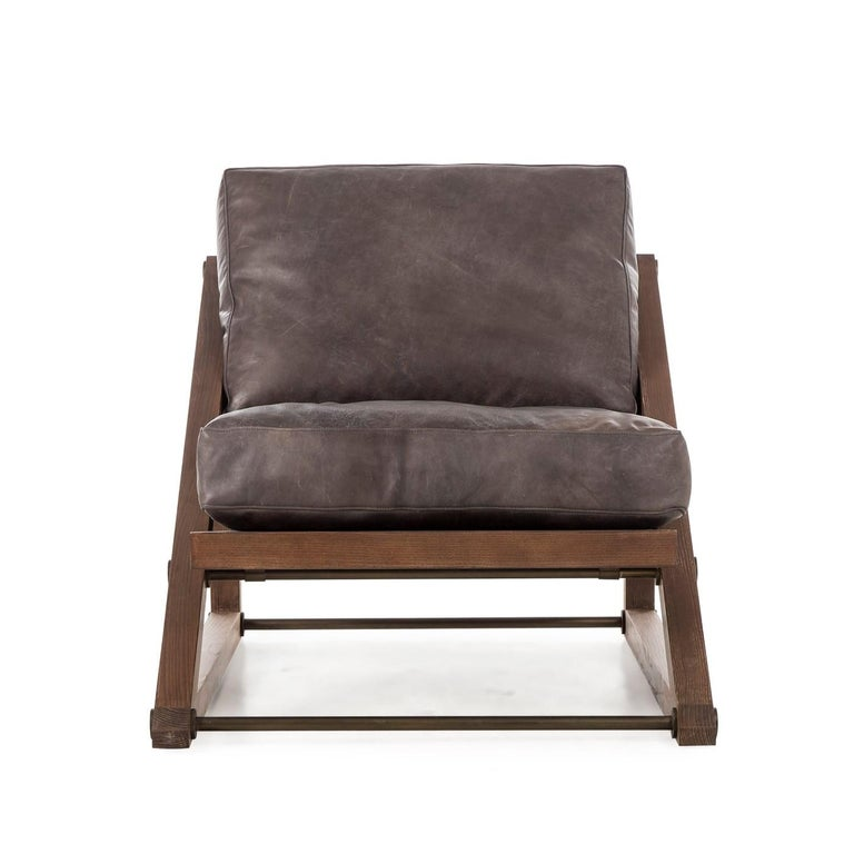 A Classic relaxer, contemporarily crafted from solid wood and accented with steel hardware finished in bronze. The contemporary Silhouette features clean lines and emphasizes comfort and style. The chair is upholstered in distressed leather in an