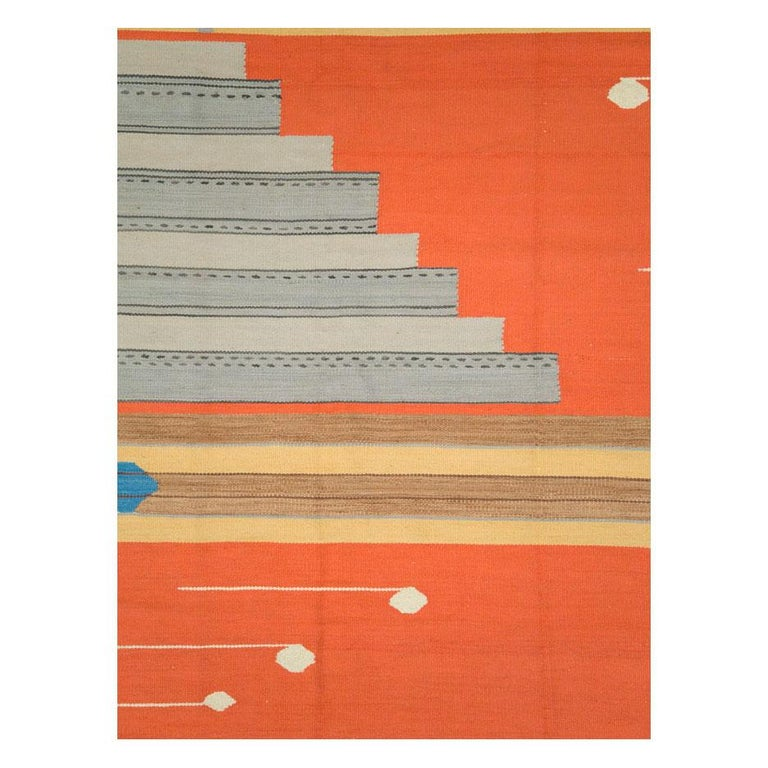 A contemporary Turkish flat-woven Kilim rug handmade during the 21st century. The overall appeal is very modern, very abstract, and very geometric - so geometric that the bitonal gray stepped motif resembles structural steel beams. The orange field