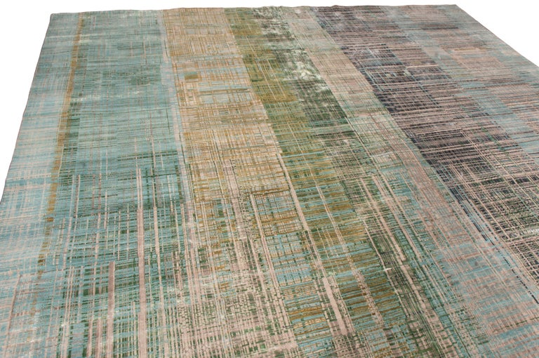 Originating from India, this contemporary geometric wool rug is hand knotted in high quality wool with a unique dual perspective to its colourways. The dominant hues of green and blue throughout the finely woven abstract scratch patterns also